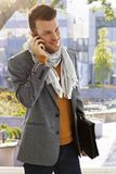 Young man on phone call outdoors. Young man talking on mobilephone outdoors at autumn stock image