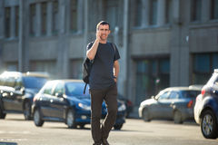 Young man on phone crossing street Stock Image
