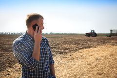 Young man with phone in a field and a tractor on a background. Stock Images