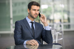 CEO Executive On A Business Call At A Cafe. Handsome young businessman in a suit and tie on a phone call Royalty Free Stock Photo