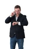 Young Man on the phone nd looking at watch Stock Photos