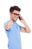 Young man on the phone pointing to you Royalty Free Stock Images