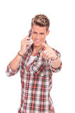 Young man on the phone pointing at you Stock Photos