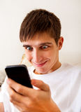 Young Man with a Phone. Surprised Young Man with Cellphone on the Sofa at the Home Royalty Free Stock Photos