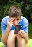 Young Man with a Phone. Surprised Young Man with a Mobile Phone in the Summer Park stock images