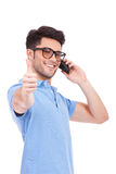 Young man on the phone thumbs up Stock Photo