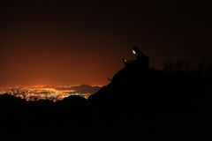 Young man with phone on top of the hill observing the night city view. Stock Images