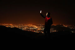 Young man with phone on top of the hill observing the night city view. Stock Photography
