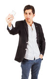 Young man with a phone on the white background Royalty Free Stock Photography