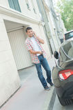 Young man phoning and unlocking car Royalty Free Stock Photo