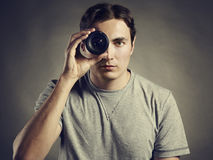 Young man photographer holding a lens in his eye Stock Photography