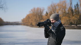 Young man Photographer With professional Camera Equipped in Black Parka Taking Pictures of Beautiful Winter park stock video footage
