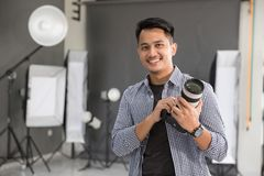 Young man photographer smiling. Handsome young photographer smiling to camera in photography studio Royalty Free Stock Photography