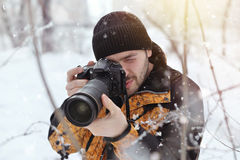The young man, a photographer takes pictures on the camera in the winter sunny day on a blurred background at the forest, Royalty Free Stock Photo