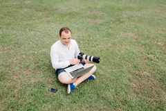 Young man photographer using laptop and camera in the park Royalty Free Stock Photography