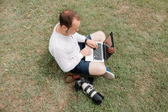 Young man photographer using laptop and camera in the park Royalty Free Stock Photos