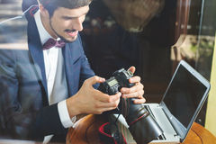 Young man photographer working at cafe, using dslr camera Royalty Free Stock Images