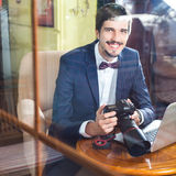 Young man photographer working at cafe, using dslr camera Royalty Free Stock Photos