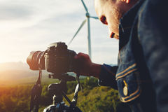 Young man photographing beautiful calm wild nature with camera of while standing against wind turbine, Royalty Free Stock Photos