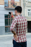 Young man photographing a building. Back view of a young man photographing a building with a small compact digital camera Royalty Free Stock Images