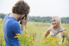 Young man photographing girlfriend in field Stock Photos