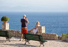 The young man photographing his girlfriend. The young men photographing his girlfriend on the coast in the city of Afitos, Halkidiki, Greece Stock Photo