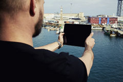 Young man photographing marina port city with touch pad. Male tourist with digital tablet camera taking picture of beautiful city from viewpoint, young man Stock Photo