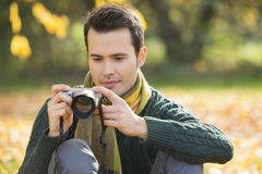 Young man photographing in park during autumn Royalty Free Stock Image