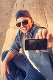Young man photographing seflie with smart phone Stock Photography