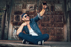 Young man photographing selefie with smart phone Stock Photography