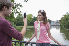 Young man photographing woman through cell phone at lakeside Royalty Free Stock Images
