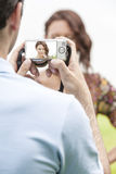 Young man photographing woman through digital camera in park Stock Image