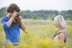 Young man photographing woman in field Stock Images