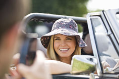 A young man photographing a young woman in a black sports car, close up Stock Photo