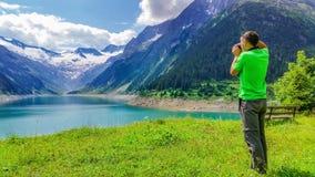 Young man photographingalpine lake, Austria Stock Photo