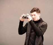 The young man photographs model the vintage camera at a wall Royalty Free Stock Photo
