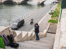 Young man photographs the Seine from stone steps leading down to Stock Photos