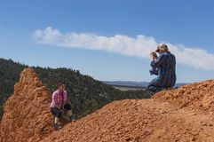 A young man photographs a young woman in Red Canyon Utah Stock Images
