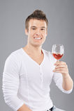 Young man pick up a wineglass Royalty Free Stock Image