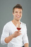 Young man pick up a wineglass Stock Photography