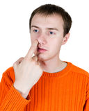 The young man is picked in a nose. Isolated Stock Photography