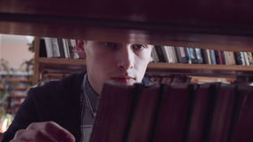 Young man picking a book stock video footage