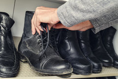 Young man picking a pair of boots from the closet. Closeup of a young caucasian man picking a pair of leather boots from the closet royalty free stock photography