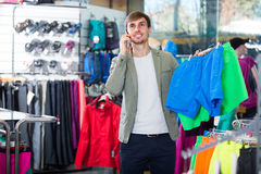 Young man picking a sport clothes Stock Images