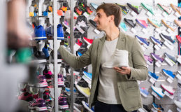 Young man picking a sporty shoes Royalty Free Stock Images