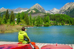 Young man at pier mountain lake with high peaks Stock Image