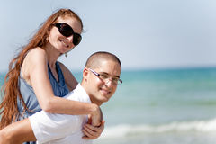 Young man piggyback his girlfriend Stock Images