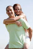 Young Man Piggybacking His Girlfriend. Happy Young Man Piggybacking His Girlfriend royalty free stock image