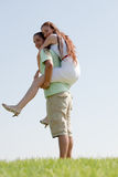 Young Man Piggybacking His Girlfriend. Happy Young Man Piggybacking His Girlfriend royalty free stock images
