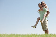 Young Man Piggybacking His Girlfriend. Happy Young Man Piggybacking His Girlfriend royalty free stock photography
